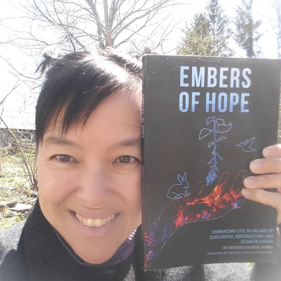 "author Bonita Eloise Ford holding her book ""Embers of Hope: Embracing Life in an Age of Ecological Destruction and Climate Chaos"""